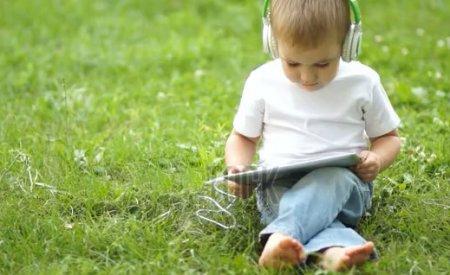 دانلود فوتیج گوش دادن به موسیفی توسط پسر بچه کوچک در پارک